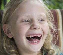 Happy young blond girl with missing front teeth